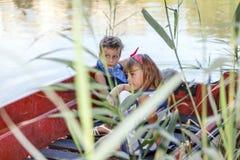 有女孩骑马的男孩在湖的一条小船在夏天晴天 库存图片
