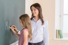 有女小学生的老师。 免版税库存图片