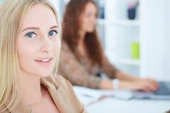 有女性同事的微笑的女实业家背景的 库存照片