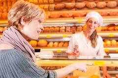 有女性客户的销售人员在面包店 图库摄影