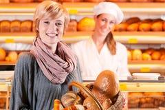 有女性客户的销售人员在面包店 免版税图库摄影