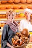 有女性客户的销售人员在面包店 库存图片