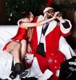 有女性护士性感的妇女的醉酒的圣诞老人狂欢节服装饮用的白兰地酒的 免版税库存图片