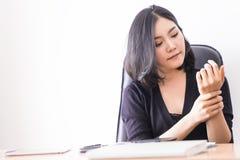 有女性的办公室工作者办公室在她的腕子的综合症状伤害 免版税库存照片