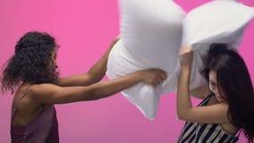 有女性的朋友在睡衣派对的滑稽的枕头战,大声笑  影视素材