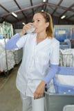 有女性自动洗衣店的工作者饮料水 免版税库存图片