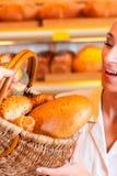 有女性顾客的推销员在面包店 免版税库存图片