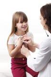 有女性医生的逗人喜爱的女孩 库存图片
