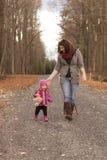 有女用连杉衬裤的妈妈和小女儿走在石渣的 免版税库存照片