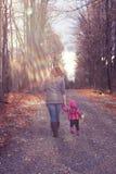 有女用连杉衬裤的妈妈和小女儿走在石渣的 库存图片