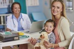 有女婴的母亲在医生的办公室 库存照片