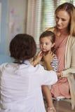 有女婴的母亲在医生的办公室 免版税图库摄影