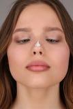 有奶油的女孩在她的鼻子 关闭 灰色背景 库存图片