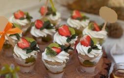 有奶油的杯沙漠和草莓和薄菏 党棒棒糖 免版税库存图片