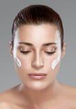 有奶油的温泉女孩在她的面孔。Skincare概念 免版税库存图片