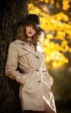 有奶油色外套、长的腿和黑帽会议的美丽的白肤金发的妇女在秋天场面 画象一非常美丽年轻典雅和 免版税库存照片
