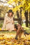 有奶油色外套、长的腿和黑帽会议的美丽的白肤金发的妇女在秋天场面 免版税图库摄影