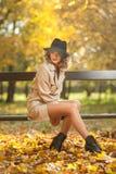 有奶油色外套、长的腿和黑帽会议的美丽的白肤金发的妇女在秋天场面 图库摄影