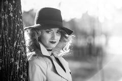 有奶油色外套、长的腿和黑帽会议的美丽的白肤金发的妇女在秋天场面 库存图片