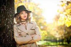 有奶油色外套、长的腿和黑帽会议的美丽的白肤金发的妇女在秋天场面 库存照片