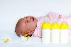 有奶瓶的逗人喜爱的新出生的女婴和安慰者 库存照片