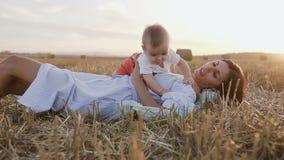 有她使用户外在领域的可爱的6个月男孩的少妇 拿着她的胳膊的一个年轻母亲一个小儿子 股票录像