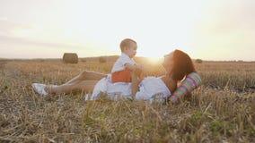 有她使用户外在领域的可爱的6个月男孩的少妇 拿着她的胳膊的一个年轻母亲一个小儿子 影视素材