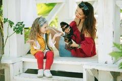 有她俏丽的妈妈的愉快的微笑的儿童女孩穿有约克夏狗逗人喜爱的小狗的时尚温暖的衣裳  免版税库存照片