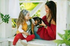 有她俏丽的妈妈的愉快的微笑的儿童女孩穿有约克夏狗逗人喜爱的小狗的时尚温暖的衣裳  免版税图库摄影