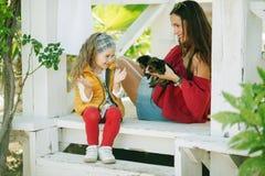 有她俏丽的妈妈的愉快的微笑的儿童女孩穿有约克夏狗逗人喜爱的小狗的时尚温暖的衣裳  库存照片