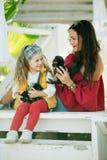 有她俏丽的妈妈的愉快的微笑的儿童女孩穿有约克夏狗逗人喜爱的小狗的时尚温暖的衣裳  库存图片