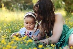 有她俏丽的小女儿的年轻母亲坐草 免版税库存图片