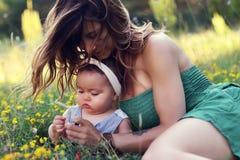 有她俏丽的小女儿的年轻母亲坐草 库存照片
