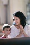 有她儿子祈祷的妇女 免版税库存图片