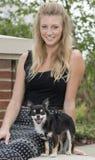 有她可爱的小狗的美丽的年轻白肤金发的妇女 免版税库存图片