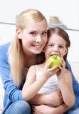 有她吃的苹果女儿的兴高采烈的妈咪 库存图片