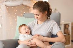 有她坐在扶手椅子的逗人喜爱的矮小的婴孩的年轻母亲 库存照片