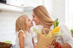 有她女儿烹调的年轻愉快的妇女 库存照片