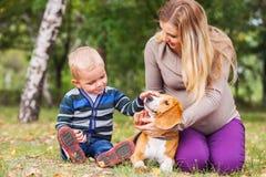有她小的儿子和宠物的怀孕的母亲在步行 免版税库存图片