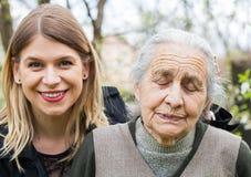 有她快乐的护工的病的老妇人 免版税库存图片