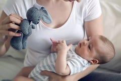 有她新出生的儿子的母亲在手上 免版税库存照片