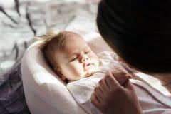 有她新出生的儿子的母亲在阳光的床放置 免版税库存图片