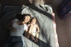 有她新出生的儿子的母亲在阳光的床放置 图库摄影
