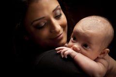 有她新出生的婴孩的可爱的种族妇女 库存照片