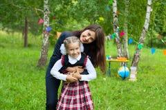 有她母亲拥抱的女小学生 免版税图库摄影