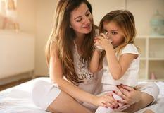 有她的一起享用在床上的女儿的母亲 免版税库存图片