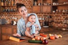 有她的一起烹调晚餐和使用数字式片剂的小儿子的母亲在厨房里 免版税库存照片