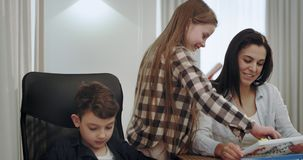 有她的一起花费时间的两个孩子的微笑时吸引人的母亲,当做家庭作业他们有一友好 股票视频