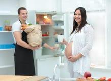 有她的丈夫的美丽的孕妇在厨房里 库存照片