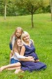 有她的三个女儿的年轻人怀孕的母亲在公园 免版税库存照片
